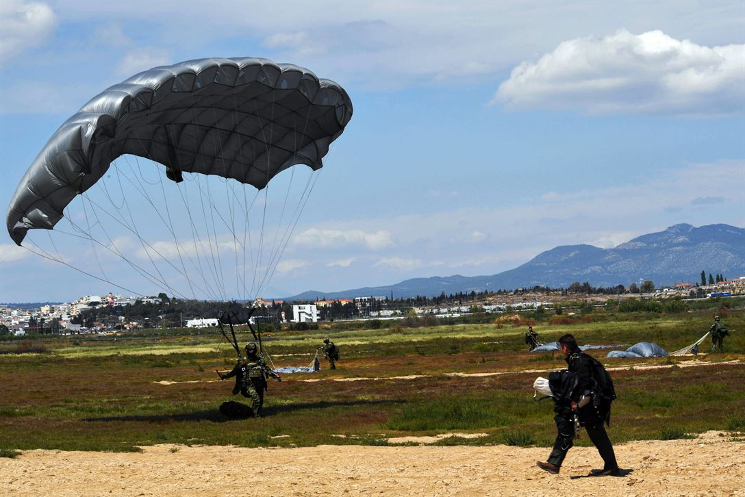 A Greek paratrooper lands at the drop zone after jumping from a U.S. Air Force C-130J Super Hercules near Megara, Greece, April 22, 2017. Approximately 80 paratroopers exited from two C-130s during static-line and free-fall jumps. As NATO allies, the U.S. and Greece share a commitment to promote peace and stability, and seek opportunities to continue developing their strong relationship. Air Force photo by Senior Airman Tryphena Mayhugh
