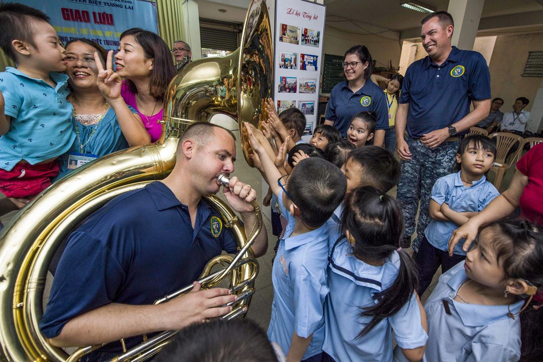 Navy Petty Officer 2nd Class James Brownell plays the tuba for hearing-impaired students as they feel the sound vibrations with their hands at Tuong Lai Specialized School in Danang, Vietnam, May 10, 2017, during Pacific Partnership 2017. Pacific Partnership is the largest annual multilateral humanitarian assistance and disaster relief preparedness mission in the Indo-Asia-Pacific region. Navy photo by Petty Officer 2nd Class Chelsea Troy Milburn