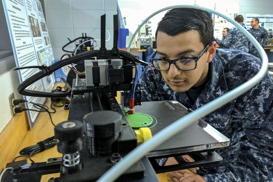 Navy Petty Officer 3rd Class Daniel Pastor examines a 3-D printer during a 3-D design and production course at Old Dominion University in Norfolk, Va., May 13, 2017, as part of the university's FleetMaker program. The program teaches service members how to design and print objects and parts that can help the fleet. Pastor is an information systems technician. Navy photo by Petty Officer 2nd Class Rawad Madanat