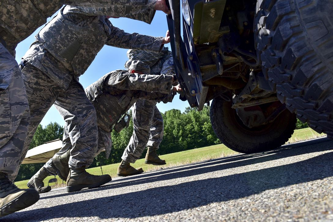 Airmen push a Humvee during the Defender Challenge at Little Rock Air Force Base, Ark., May 15, 2017. The base held the team competition, which also included a four-mile ruck march, buddy carries and a blindfold weapon dismantling contest, to kick off Police Week 2017. Air Force photo by Staff Sgt. Jeremy McGuffin