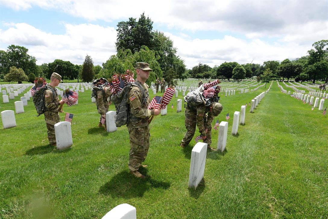 """Soldiers place American flags in front of headstones during """"Flags In"""" at Arlington National Cemetery in Arlington, Va., May 25, 2017. The soldiers, assigned to the 3rd U.S. Infantry Regiment known as """"The Old Guard,"""" placed more than 284,540 grave markers to honor every individual buried at Arlington National Cemetery. DoD photo by Sebastian J. Sciotti Jr."""