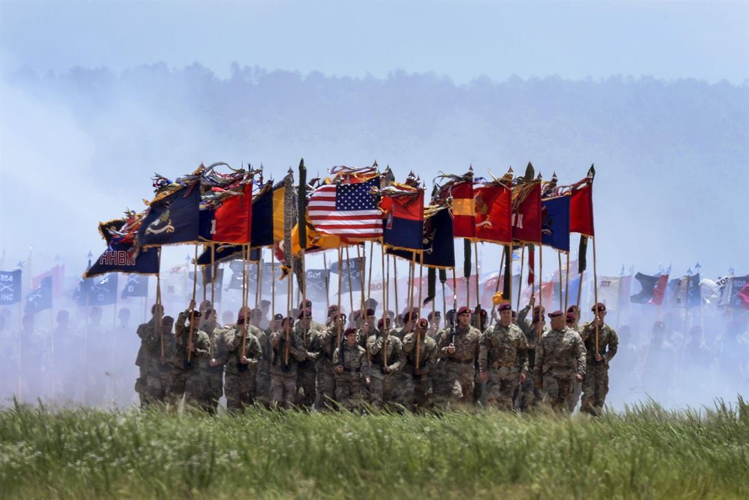 Soldiers carry flags as they march off Sicily drop zone during an airborne review at Fort Bragg, N.C., May 25, 2017. The review is the culminating event of 100th All American Week. The soldiers are assigned to the 82nd Airborne Division. Air Force photo by Senior Airman Ericka Engblom