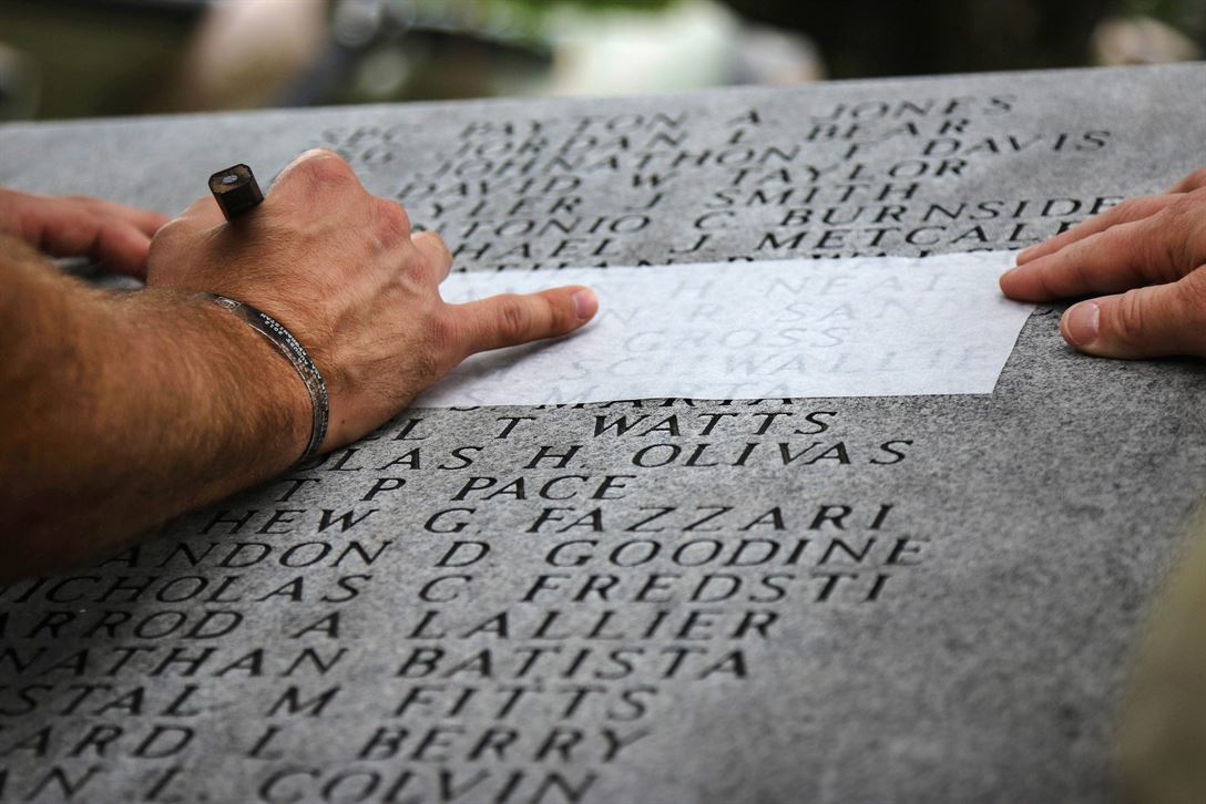 Gold Star families create rubbings of etched names on the Global War on Terrorism Memorial during the All American Week Memorial Service at the 82nd Airborne Division War Memorial Museum at Fort Bragg, N.C., May 24, 2017. The service allows troops, family members and friends to recognize the 5,021 paratroopers who died in combat and 236 paratroopers who died in training during the division's century of service. Army photo by Sgt. Jessica Nassirian