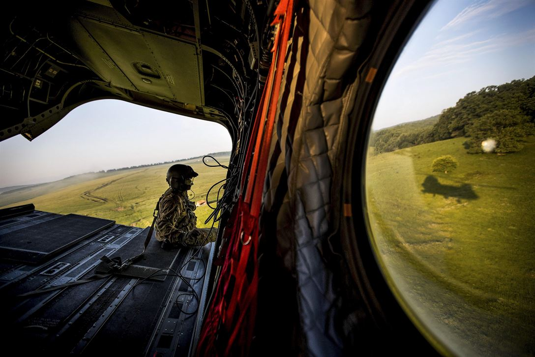 An Air Force loadmaster sits on the ramp of a Chinook helicopter flying over the Cincu Training Area in Romania, June 6, 2017, during training with British Grenadier Guards. Allied Joint Force Command Naples courtesy photo