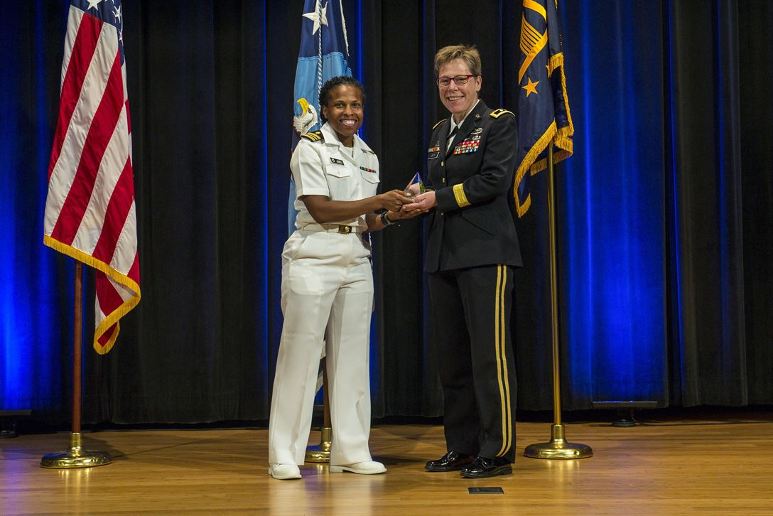 Navy Lt. Cmdr. Damita Zweiback presents a Department of Defense Pride Military Leadership Award to Army Maj. Gen. Tammy S. Smith, deputy commanding general for sustainment of the Eighth Army, during an award ceremony marking LGBT Pride Month at the Pentagon, June 12, 2017. Army photo by Zane Ecklund