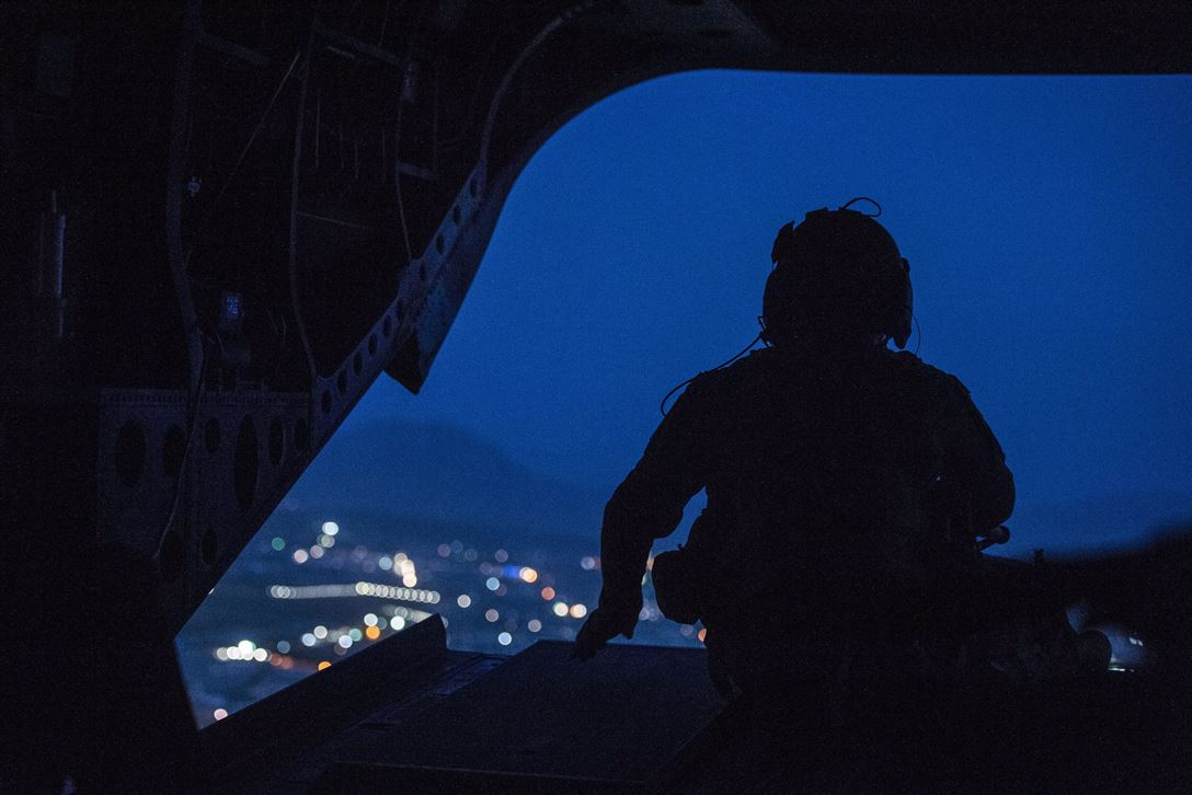 A CH-47 Chinook helicopter crew chief keeps watch during a flight over Kabul, Afghanistan, April 24, 2017. The helicopter was carrying Defense Secretary Jim Mattis as he visited the country. DoD photo by U.S. Air Force Tech. Sgt. Brigitte N. Brantley