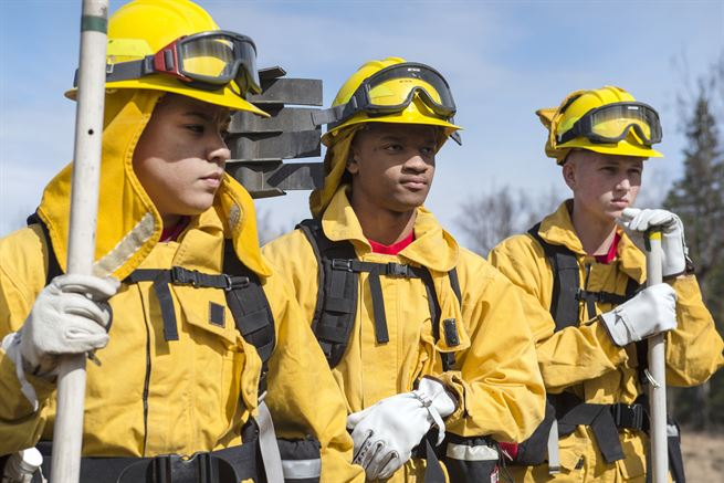 Airmen receive a mission briefing before conducting a controlled burn at the Infantry Platoon Battle Course at Joint Base Elmendorf-Richardson, Alaska, May 4, 2017. The airmen are fire protection specialists assigned to the 673d Civil Engineer Squadron. They worked with U.S. Forest Service personnel to manage controlled burns of dry brush and grass. Air Force photo by Alejandro Pena