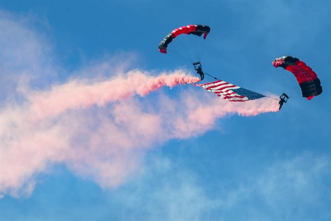 Army paratroopers descend through the sky with the American flag during the opening ceremony of the South Carolina National Guard Air and Ground Expo at McEntire Joint National Guard Base, S.C., May 6, 2017. The paratroopers are assigned to the Black Daggers, the official U.S. Army Special Operations Command Parachute Demonstration Team. The expo showcases South Carolina National Guard airmen and soldiers. Army National Guard photo by Sgt. Brian Calhoun