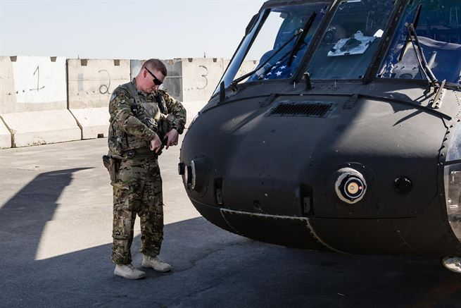 A soldier secures his gear outside a UH-60 Black Hawk helicopter before a flight at Kandahar Airfield, Afghanistan, May 27, 2017. The pilot is assigned to the 7th Infantry Division's 16th Combat Aviation Brigade, Task Force Warhawk. Army photo by Capt. Brian Harris