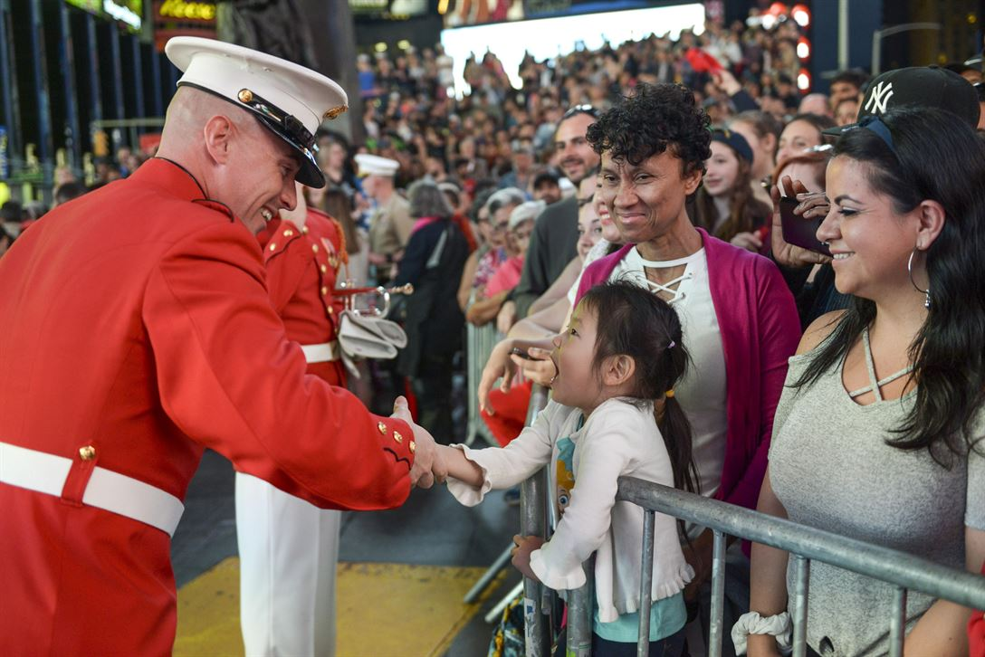 A Marine Drum and Bugle Corps member greets a young fan after performing in Times Square in New York City as part of Fleet Week New York, May 27, 2017. Sailors, Marines and Coast Guardsmen demonstrate capabilities and teach the people of New York about America's sea services during the yearly observance. Marine Corps photo by Lance Cpl. Samantha Bray