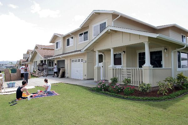 Navy family members relax on their front lawn while movers deliver household goods to their new home on Ford Island.