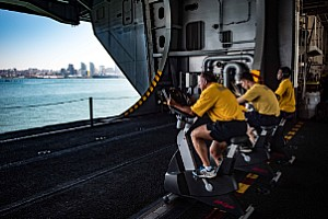 Sailors conduct their bi-annual Physical Readiness Test (PRT) on stationary bikes in the hangar bay of the aircraft carrier USS Theodore Roosevelt (CVN 71).