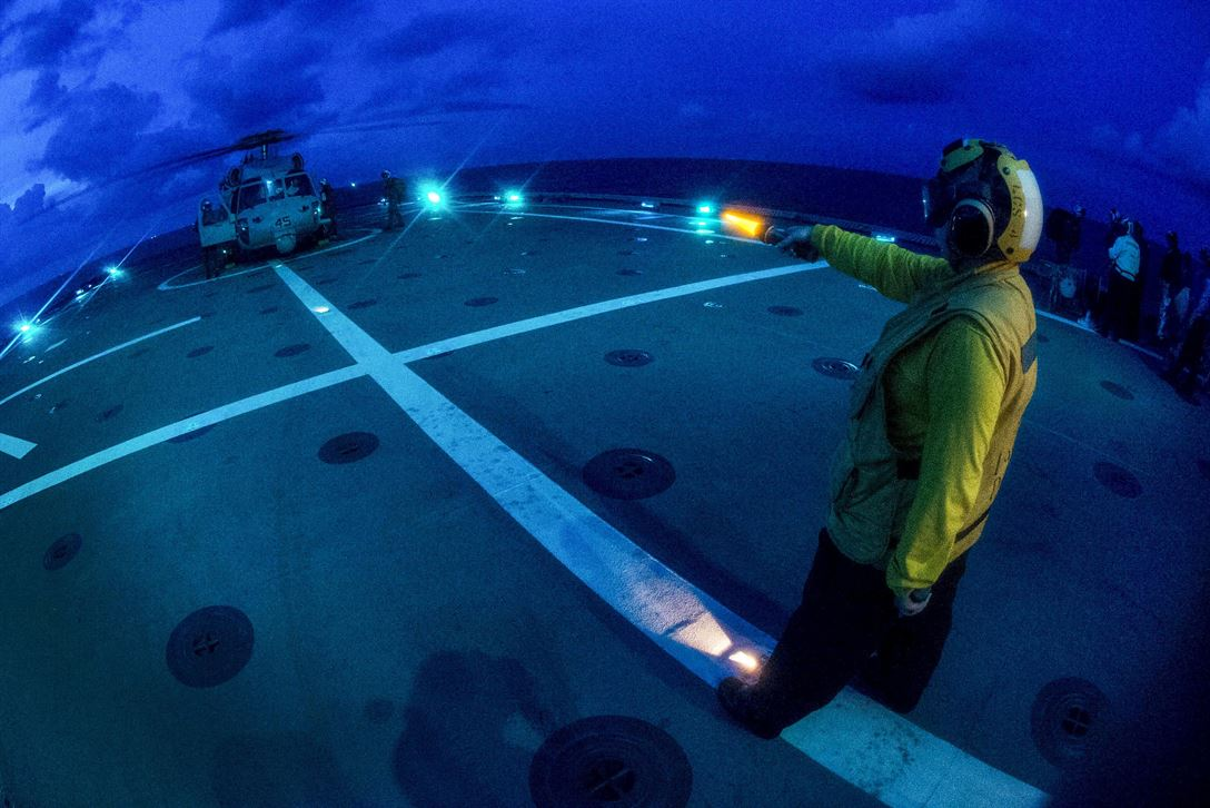 Navy Petty Officer 1st Class Alishia Miller signals to the pilots of an MH-60S Seahawk helicopter aboard the USS Coronado in the Gulf of Thailand, June 2, 2017, during flight operations as part of the annual Cooperation Afloat Readiness and Training Thailand exercise. Navy photo by Petty Officer 3rd Class Deven Leigh Ellis