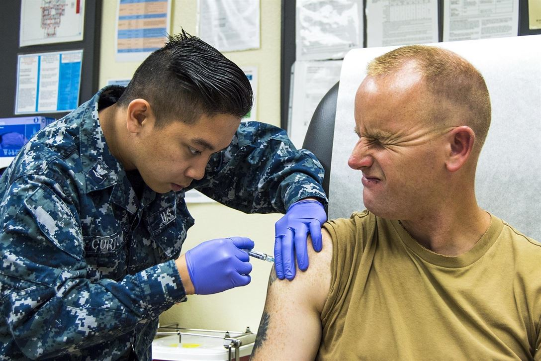 Navy Petty Officer 2nd Class Charles Scheck winces as Petty Officer 3rd Class Gerich Curtom administers a flu shot at Naval Air Station North Island's medical clinic in Coronado, Calif., June 3, 2017. Scheck is a builder and Curtom is a hospital corpsman. Navy photo by Petty Officer 1st Class Sean P. Lenahan