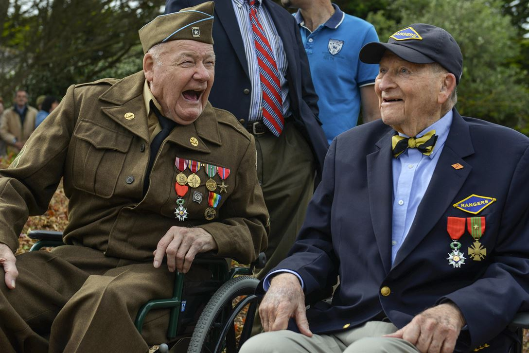 Two D-Day veterans who participated in the liberation of France share a laugh in Saint-Laurent-sur-Mer, France, June 5, 2017, while attending a ceremony to commemorate the 73rd anniversary of D-Day. DoD photo by Airman 1st Class Alexis C. Schultz