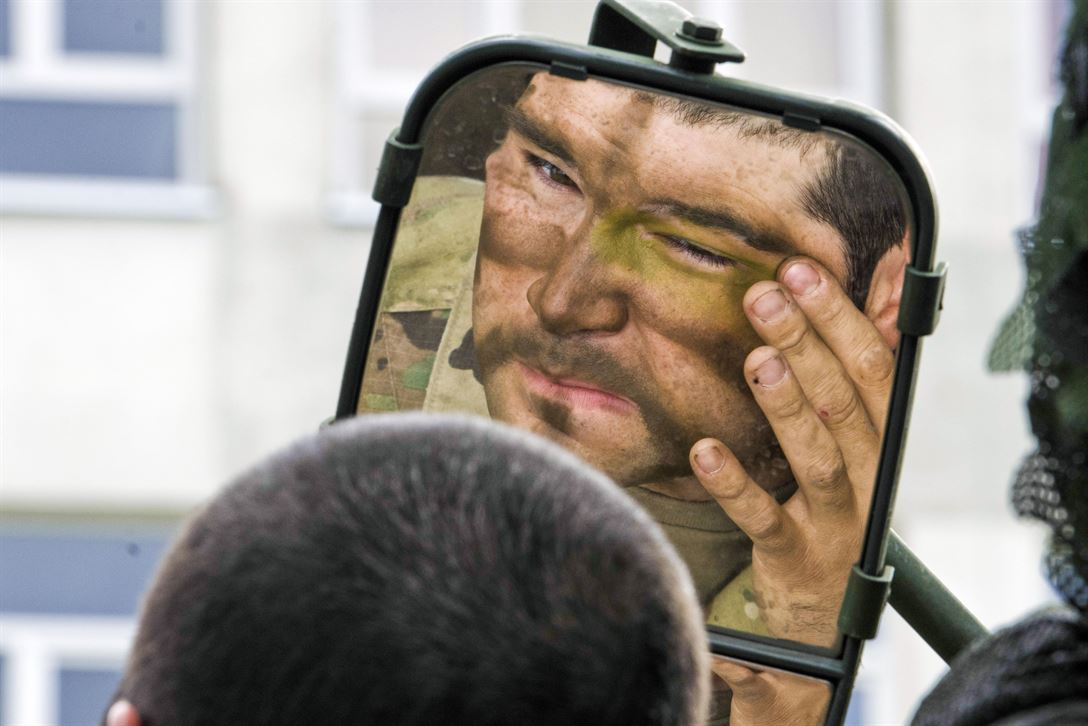A soldier uses the mirror on his Stryker vehicle to paint his face before a multinational field training exercise as part of Saber Strike 17 in Bemowo Piskie, Poland, June 13, 2017. Saber Strike is an annual U.S. Army Europe-led exercise aimed at enhancing the NATO alliance throughout the Baltic region and Poland. Army photo by Sgt. Justin Geiger